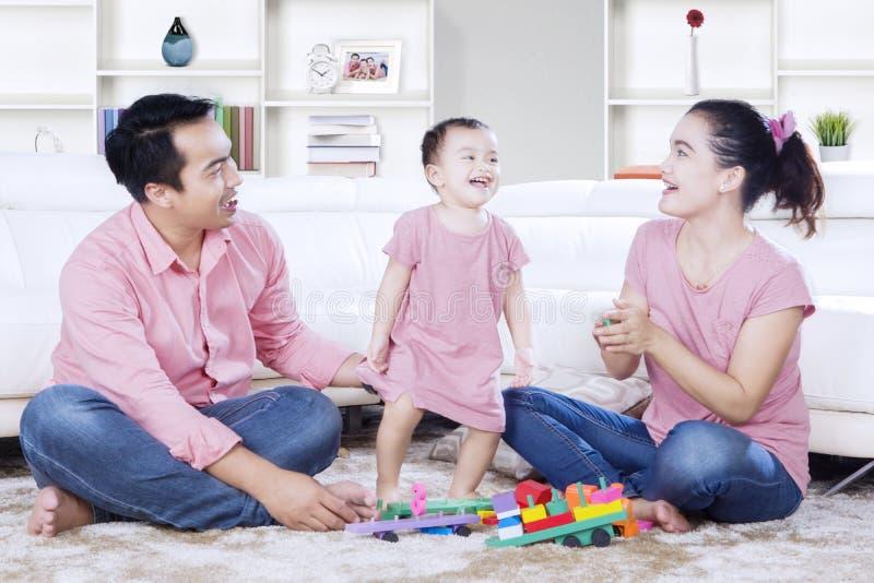 Маленькая девочка смотрит счастливой с ее родителями стоковые изображения rf