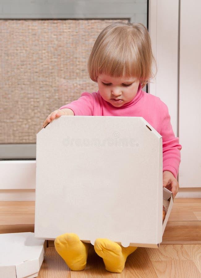 Маленькая девочка смотря в коробку с пиццей стоковые изображения rf