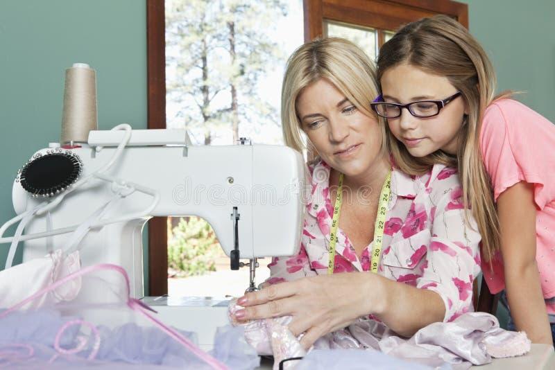 Маленькая девочка смотря ткань матери шить стоковая фотография