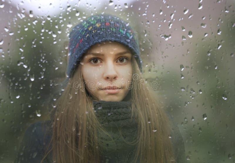 Маленькая девочка смотря через окно с дождевыми каплями стоковое фото