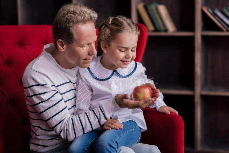 Маленькая девочка смотря яблоко с ее дедом стоковые фото