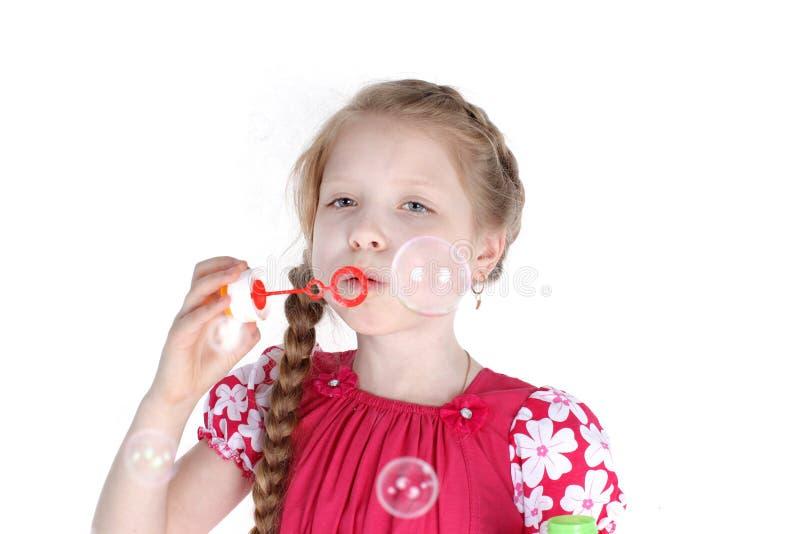 Маленькая девочка 8 старых дуя лет пузырей мыла стоковые фото