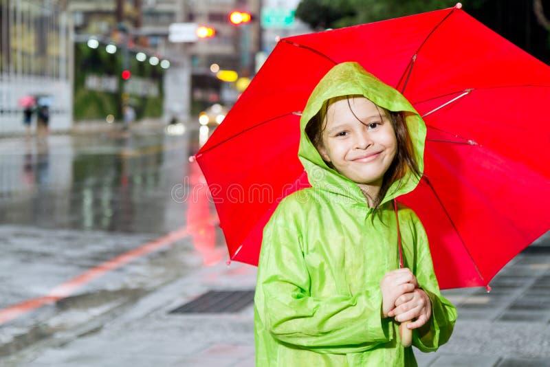 Маленькая девочка стоя в дожде с плащом и зонтиком стоковая фотография rf