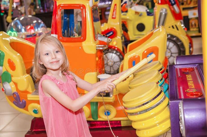 Маленькая девочка стоя и играя барабанчики на крытом парке атракционов стоковая фотография rf