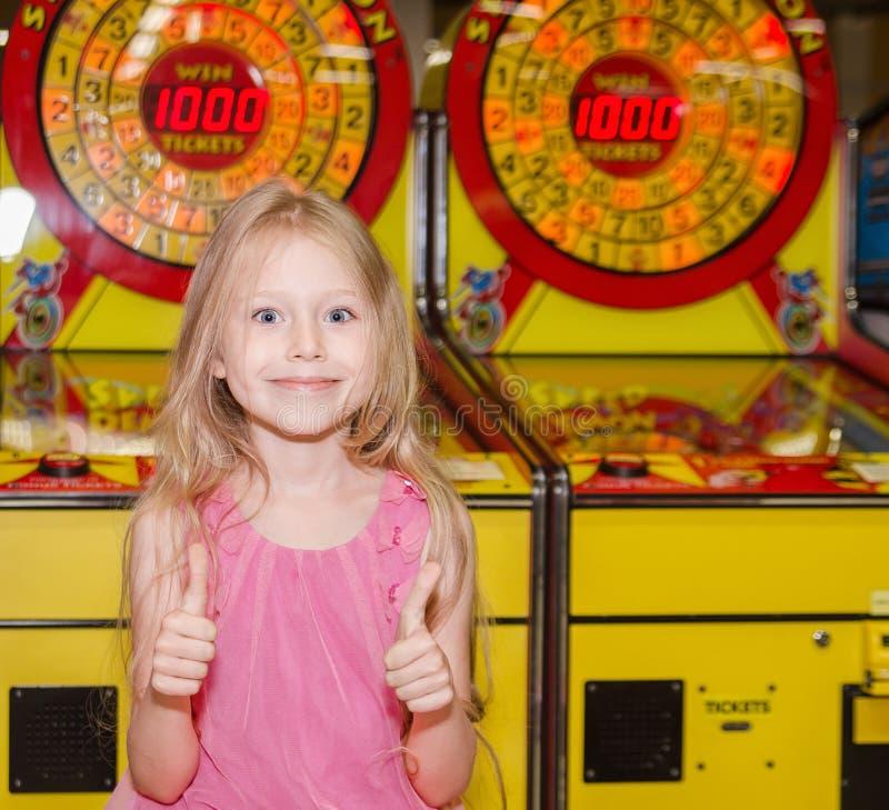 Маленькая девочка стоя и играя на крытом парке атракционов стоковые фотографии rf