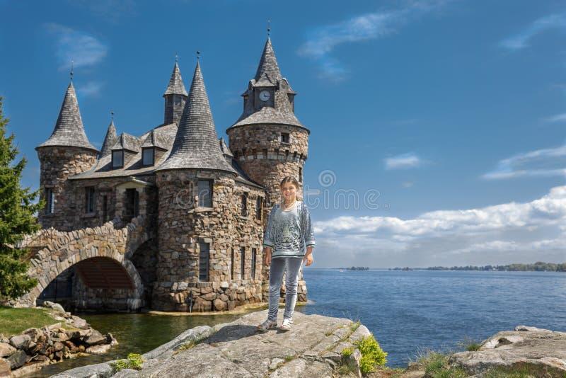 Маленькая девочка стоя на большом утесе около озера против старого винтажного замка стоковая фотография rf