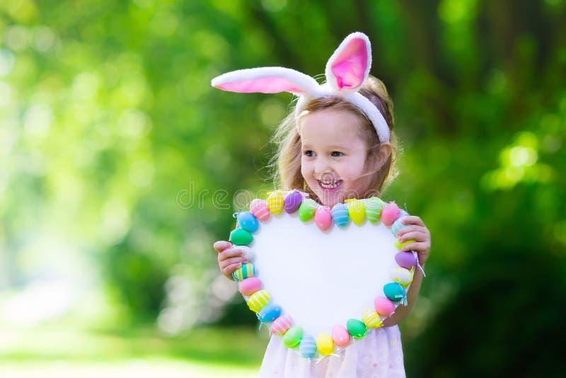 Маленькая девочка с белой доской для приветствий пасхи стоковые изображения rf
