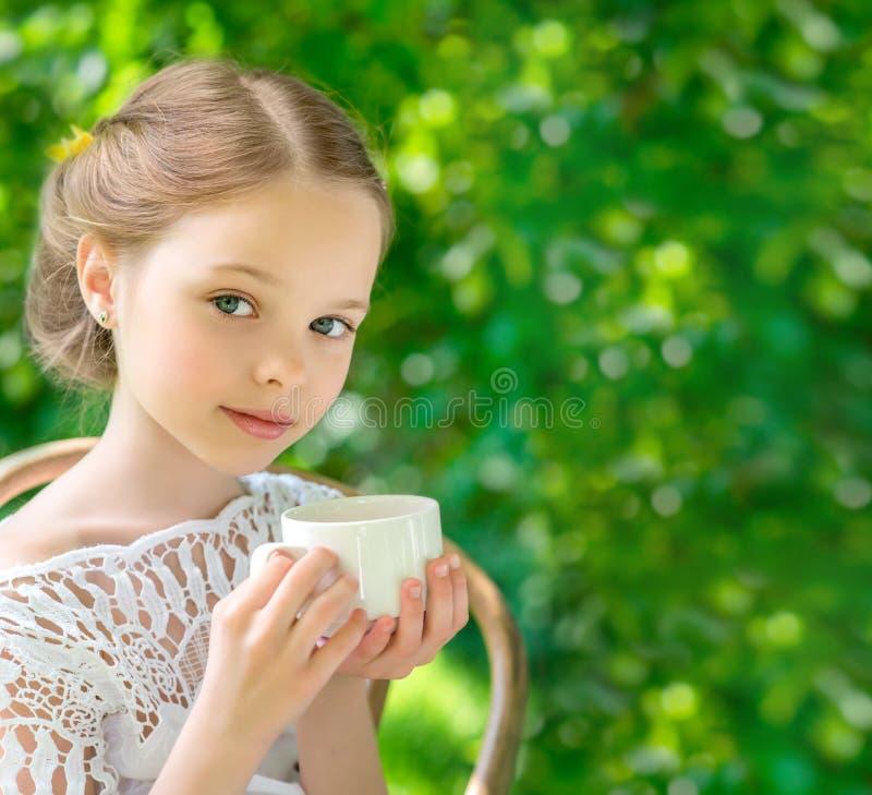 Маленькая девочка с белой чашкой внешней стоковая фотография