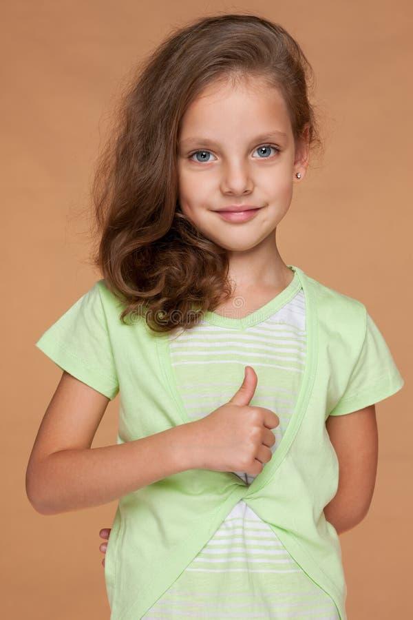 Маленькая девочка с ее большим пальцем руки вверх стоковые фотографии rf
