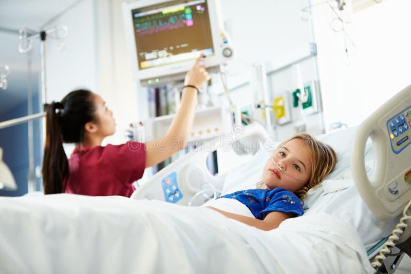 Маленькая девочка с женской медсестрой в отделении интенсивной терапии стоковая фотография