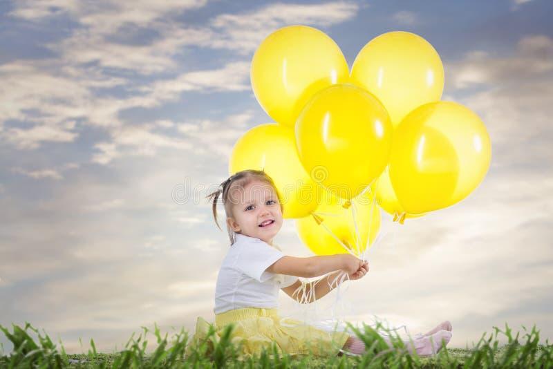 Маленькая девочка с желтыми воздушными шарами стоковое изображение rf