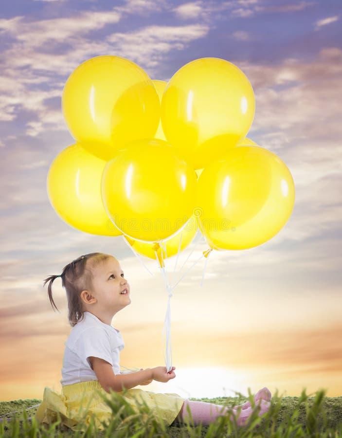 Маленькая девочка с желтыми воздушными шарами стоковое фото