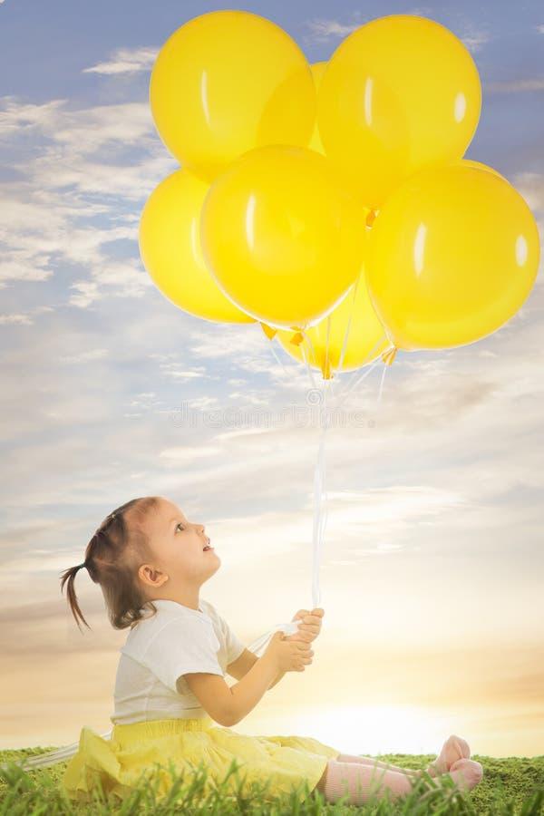 Маленькая девочка с желтыми воздушными шарами стоковые фото