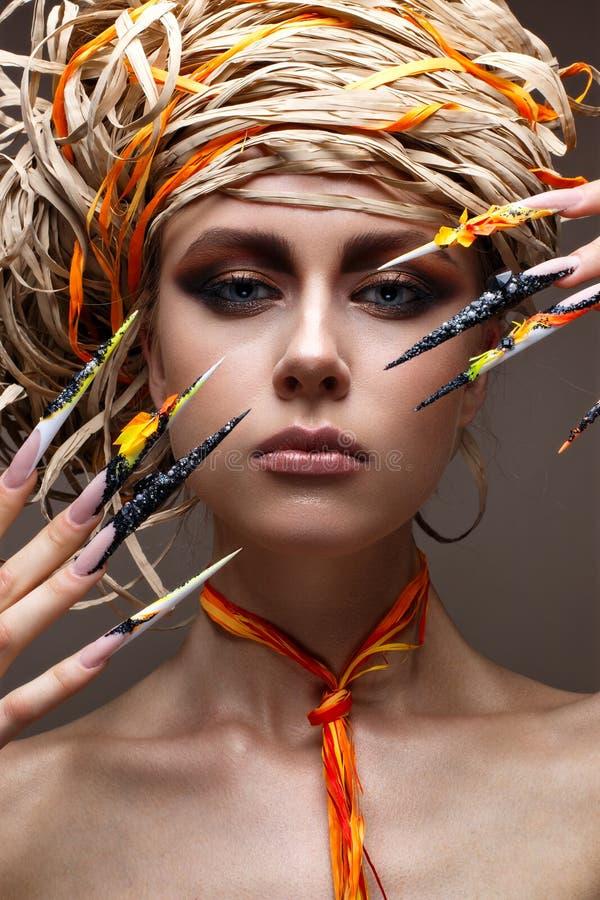 Маленькая девочка с длинными украшенными ногтями и ярким творческим составом Красивая модель с соломенной шляпой на ее голове Кра стоковые фото
