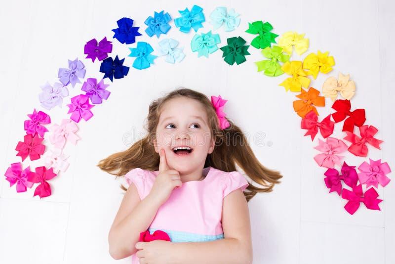Маленькая девочка с красочным смычком вспомогательная белизна hairpin волос стоковые изображения