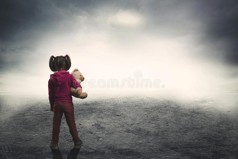 Маленькая девочка с медведем игрушки в темноте стоковые изображения rf