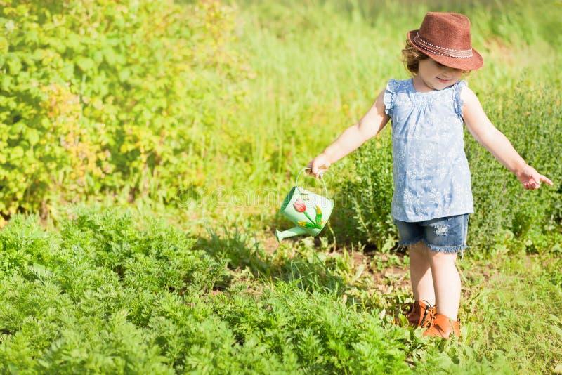 Маленькая девочка с моча чонсервной банкой в саде стоковое изображение