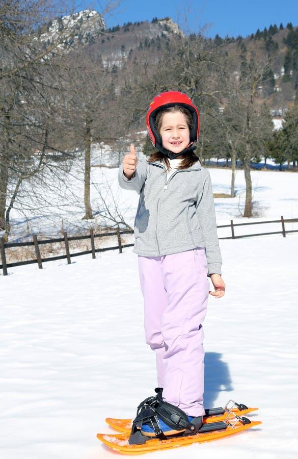 Маленькая девочка с оранжевыми snowshoes и шлемом стоковое изображение rf
