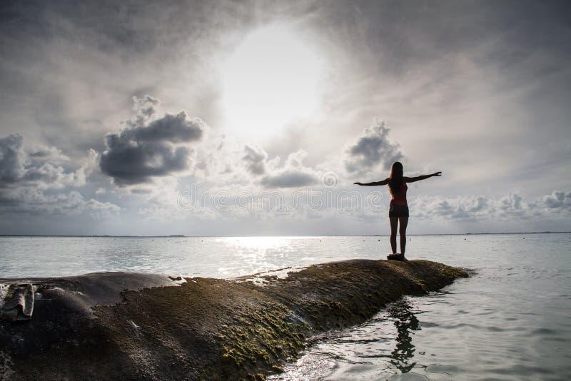 Маленькая девочка с открытыми оружиями на море стоковая фотография rf