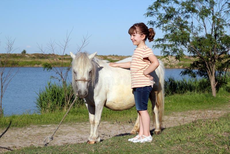 Маленькая девочка с лошадью пониа стоковая фотография rf