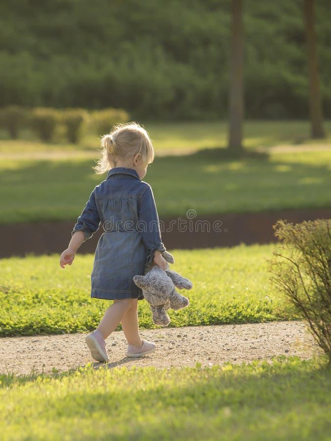 Маленькая девочка с плюшем для прогулки в парке стоковые изображения rf
