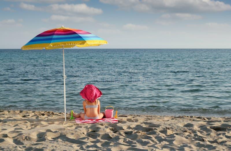 Маленькая девочка с сидеть под навесом на пляже стоковые фотографии rf