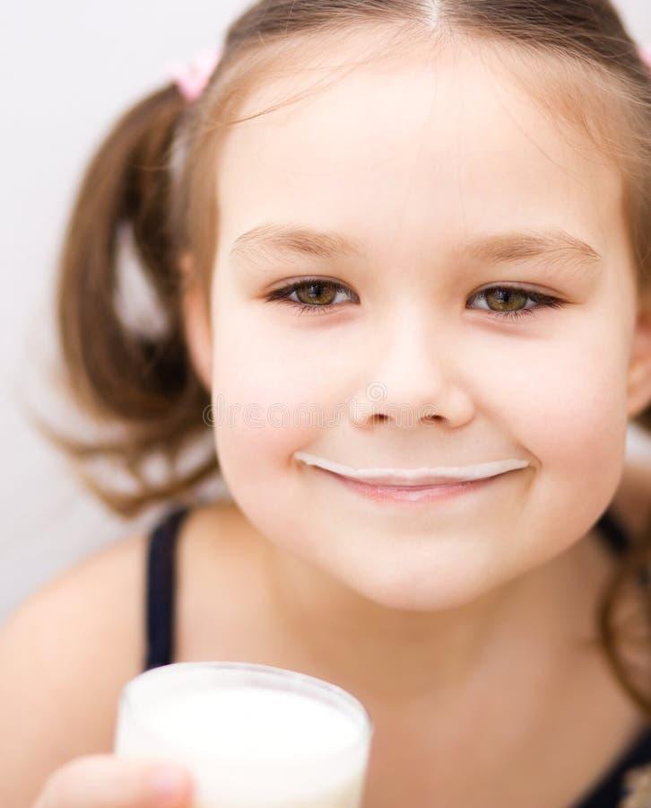 Маленькая девочка с стеклом молока стоковые изображения rf