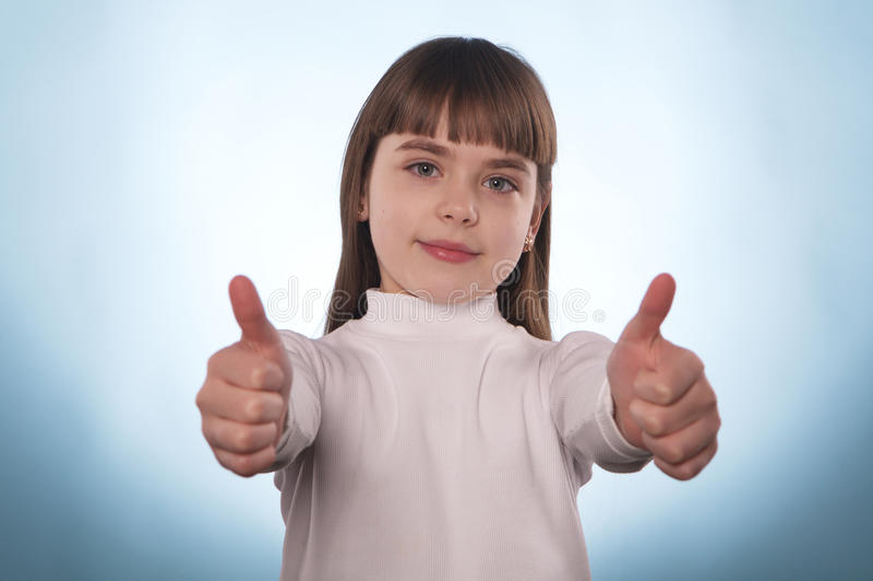 Маленькая девочка с указательным пальцем вниз или поднимает изолированный стоковые изображения