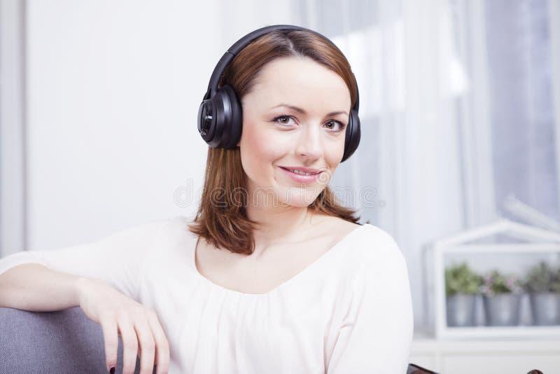 Маленькая девочка слушает к музыке с наушниками стоковая фотография rf