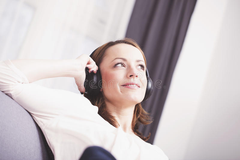 Маленькая девочка слушает к музыке с наушниками стоковые фотографии rf