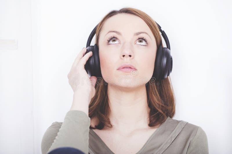 Маленькая девочка слушает к музыке с наушниками стоковое изображение rf
