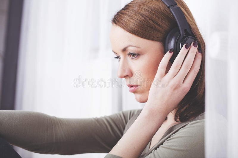 Маленькая девочка слушает к музыке с наушниками стоковая фотография