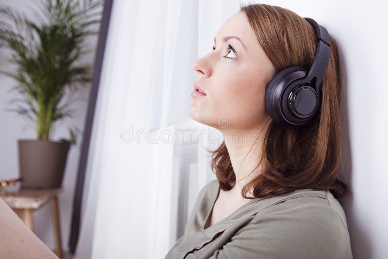 Маленькая девочка слушает к музыке с наушниками стоковое фото rf