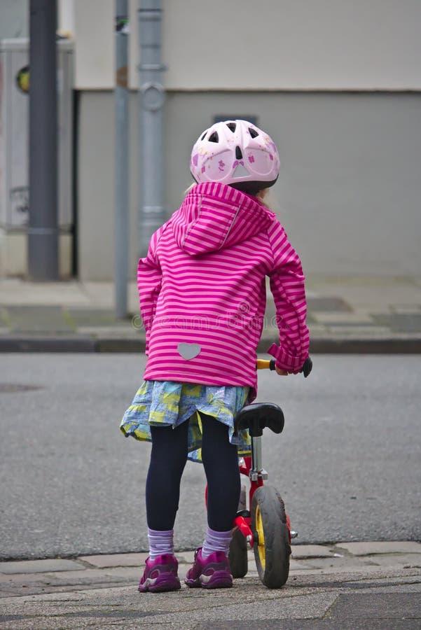 Маленькая девочка с шлемом велосипеда и баланс велосипед ждать для того чтобы пересечь улицу стоковое изображение rf