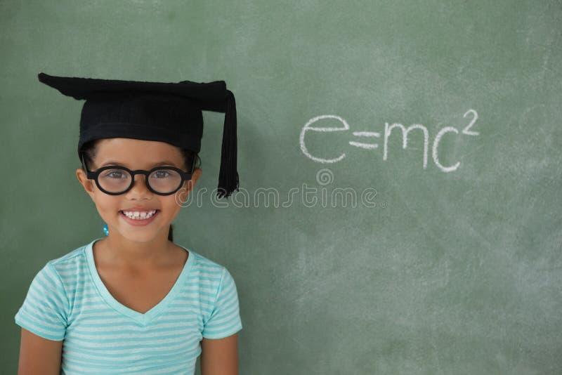 Маленькая девочка с шляпой градации против доски мела стоковое фото