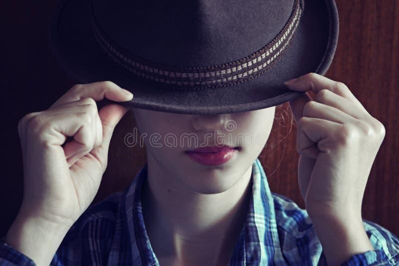 Маленькая девочка с шляпой Прячет ее сторону Депрессия Подкрашиванное фото стоковые изображения