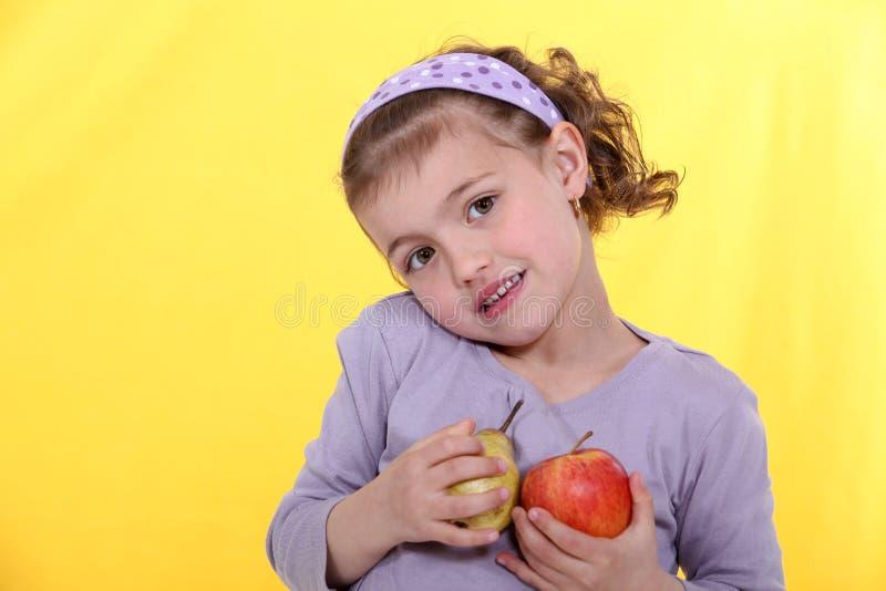 Маленькая девочка с яблоками стоковые фото