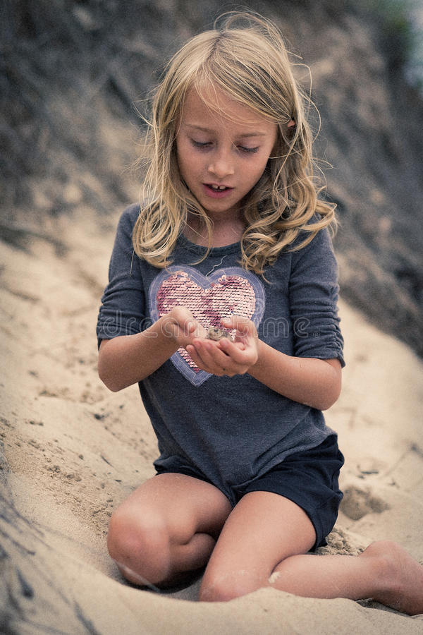 Маленькая девочка с лягушкой на пляже стоковое изображение rf