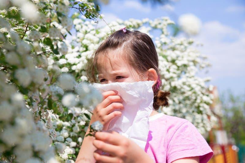 Маленькая девочка дует ее нос стоковая фотография