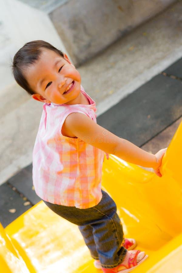 Маленькая девочка усмехаясь на слайдере стоковое изображение