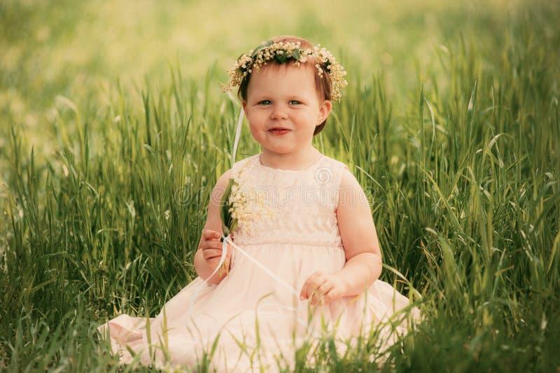 Маленькая девочка усмехаясь, ребенок сидя на траве стоковая фотография rf