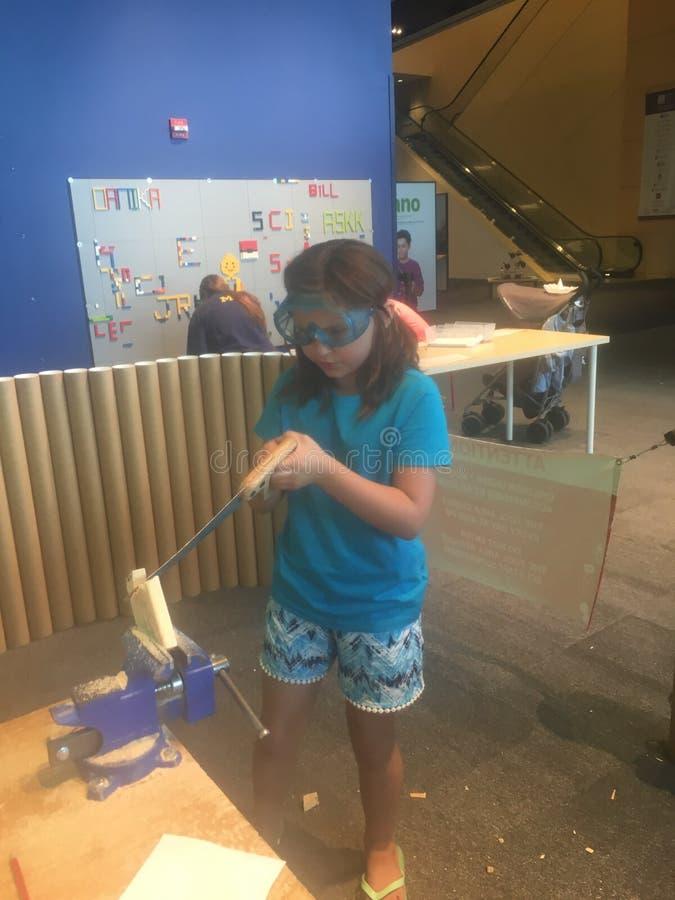 Маленькая девочка уча использовать ручную пилу стоковое изображение