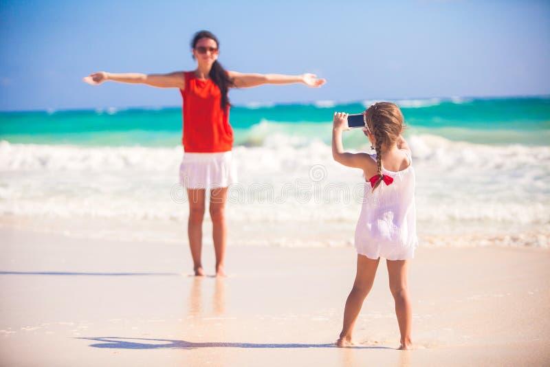 Маленькая девочка фотографирует ее мать на пляже стоковые фото