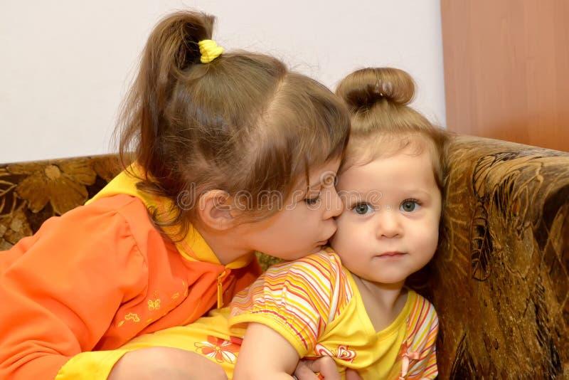Маленькая девочка целует более молодую маленькую сестру стоковая фотография rf