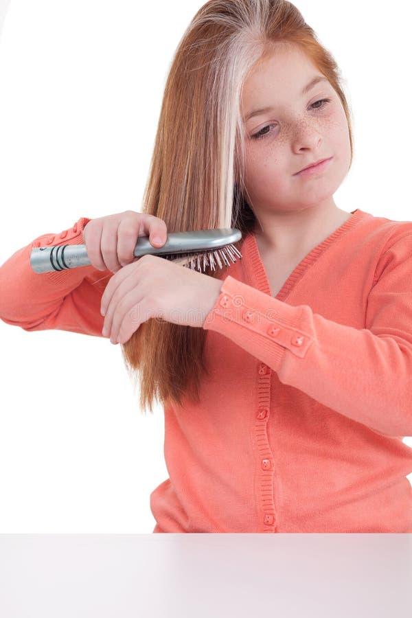 Маленькая девочка чистя ее волосы щеткой стоковые изображения