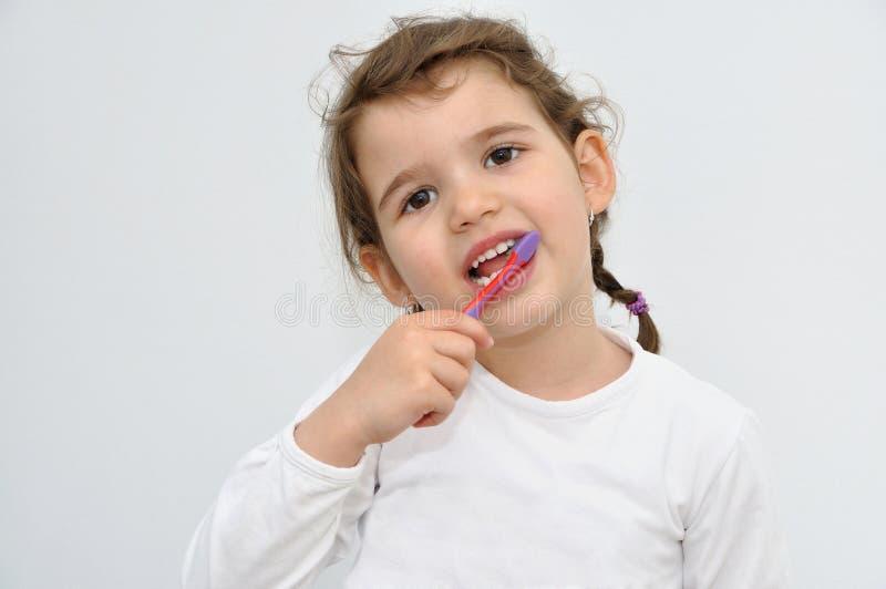Маленькая девочка чистя зубы щеткой стоковые изображения rf