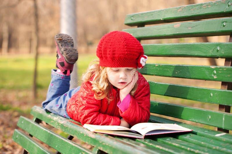 Маленькая девочка читая книгу стоковые изображения