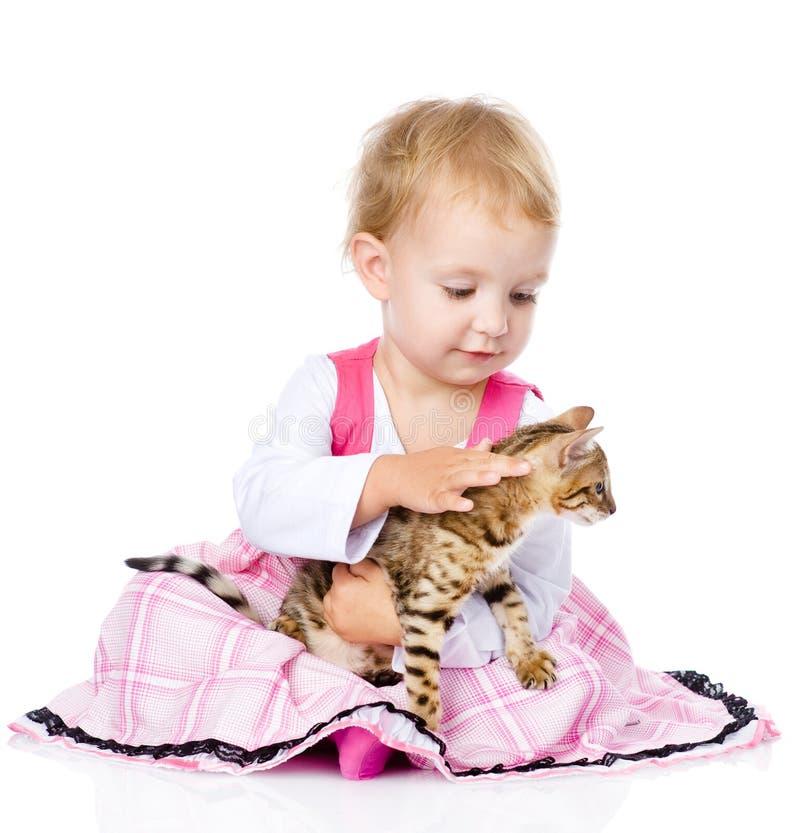 Маленькая девочка patting котенок На белой предпосылке стоковое фото
