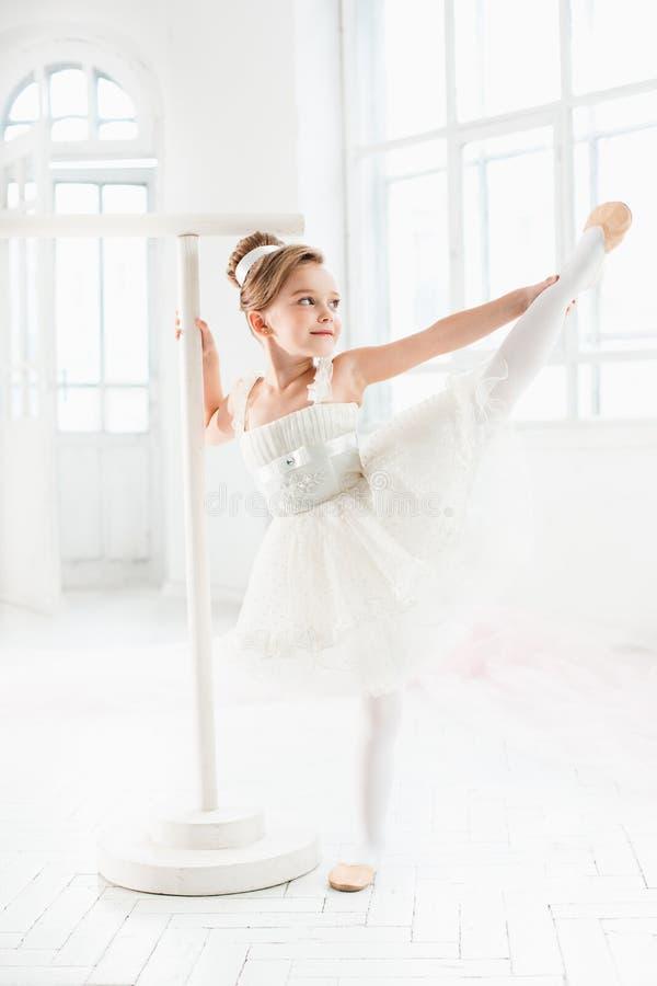 Маленькая девушка балерины в балетной пачке Прелестный ребенок танцуя классический балет в белой студии стоковые фото