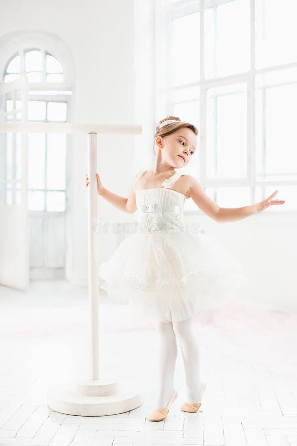Маленькая девушка балерины в балетной пачке Прелестный ребенок танцуя классический балет в белой студии стоковое изображение rf